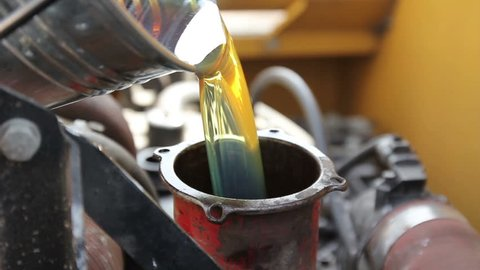 combine technical services. mechanic pours oil from the bucket into the oil filler