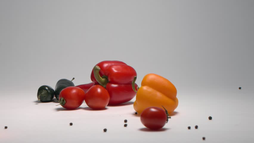 Fresh falling vegetables: orange and red peppers, green and red chili peppers, jalapeno, cherry tomatoes, black pepper on white background scattering in different directions. Slow motion 120fps.