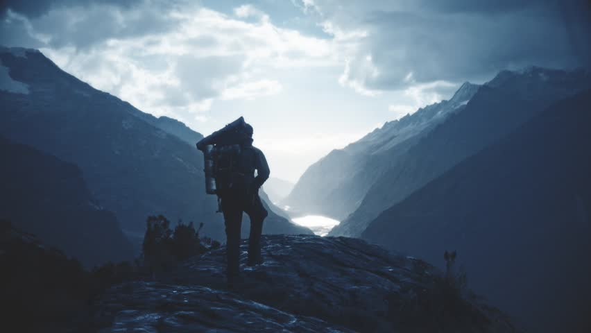 Silhouette of backpacker walking towards the edge of a rocky peak to contemplate the beautiful panorama of the Huascaran National Park. Slow motion | Shutterstock HD Video #21402010