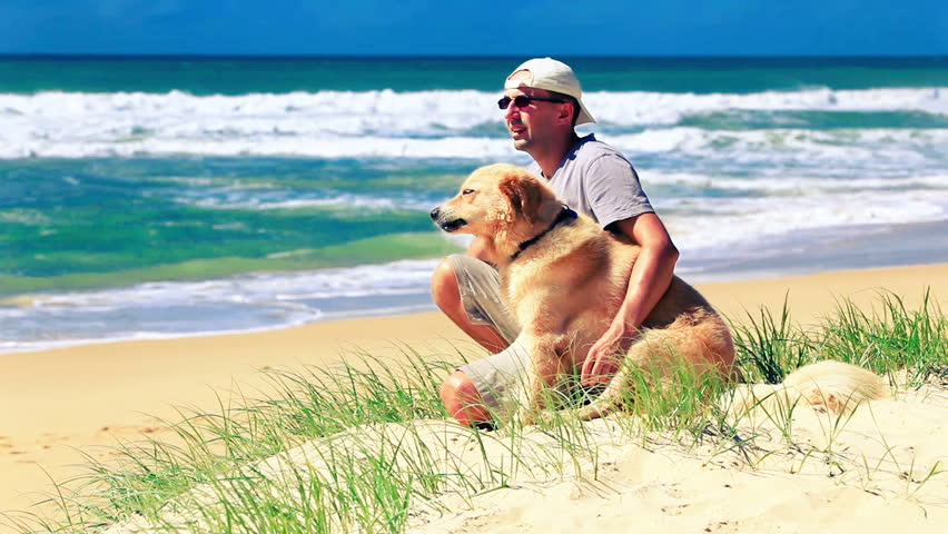 Male owner sitting on a beach with a dog