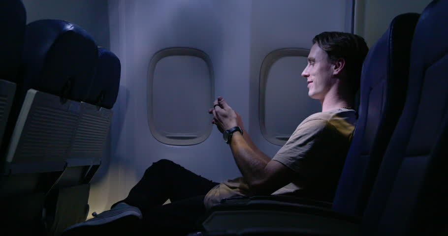 Handsome young man using a cellphone on airliner at night. Medium long shot from side angle,  recorded hand-held at 60fps