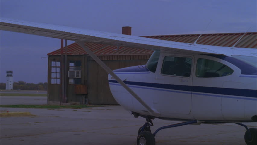 DUSK Small private plane Cessna taxis away, small hangar ND airport