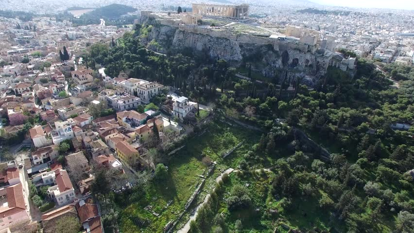 Aerial drone bird-eye view moving up for flight around the Acropolis of Athens ancient citadel located on rocky outcrop showing Parthenon very famous tourist attraction in Europe Greece great city 4k