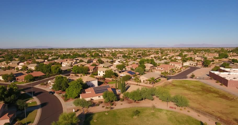 A flyover aerial establishing shot of a typical Arizona residential neighborhood. The Superstition Mountain range in the distance. Phoenix suburb.
