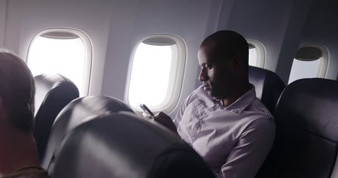 View across seats of African American man sitting next to window and texting on phone in main cabin of commercial airliner.  Medium shot from side angle, recorded hand held at 60fps.