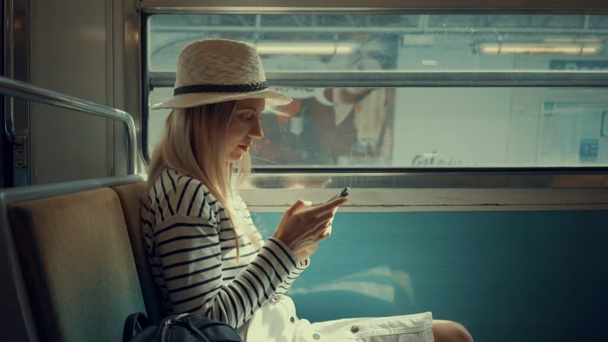 Woman tourist sitting at train and looking to mobil phone near the Eiffel tower at sunny day in Paris. Famous popular touristic place in the world.  | Shutterstock HD Video #21529885