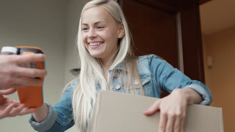 Smiling Homeowner Receives Postal Parcel and Signs Electronic Signature Deivce. While Standing in the Open Doorway. Shot on RED Cinema Camera in 4K (UHD).