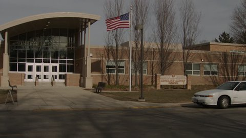 day pan along small Midwest Highland Middle School American Flag blowing wind, brick school, tan brick building modern glass entrance many glass doors, elementary school (Jan 2013)
