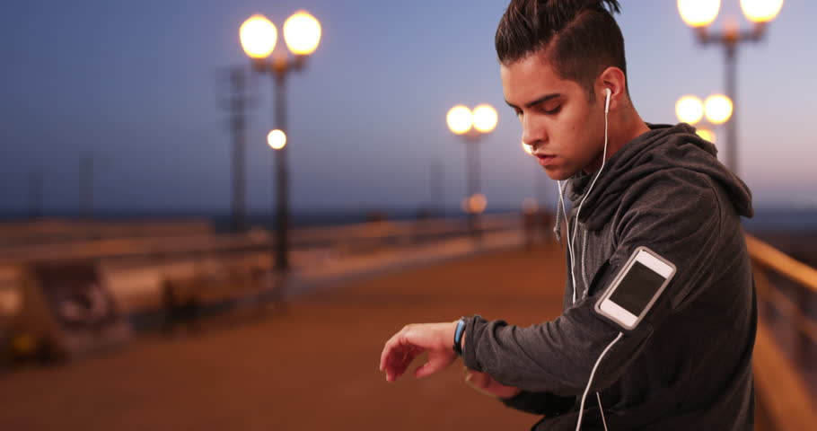 Millennial Hispanic Jogger checking fitness tracker while resting on boardwalk. Latino runner jogging on pier listening to music with smartphone and earbuds. 4k