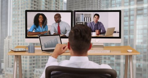 Hispanic business man in high rise corporate office having internet video conference with diverse group of coworkers. Businessman and international colleagues communicating over VoIP
