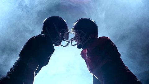Two guys football player facing their helmets in the smoke. Slow motion