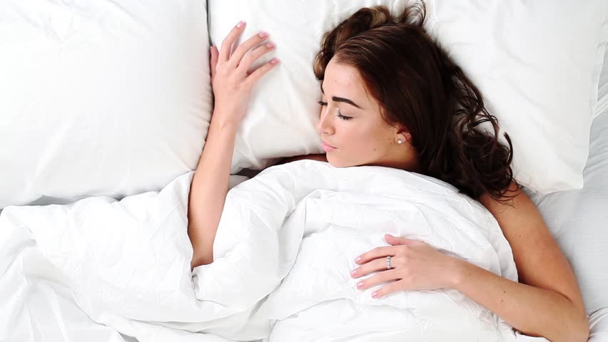 Fresh and happy woman in bed wakes up in the morning smiling