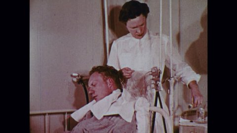 UNITED STATES 1950s: Woman attaches electrodes to man's head / Close up, hands attach electrodes / Woman attaches electrodes / Man sleeping, woman leaves room.