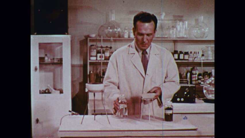 UNITED STATES 1950s: Man in lab pours liquids into bowl, walks away, bowl begins to smoke. | Shutterstock HD Video #21579712