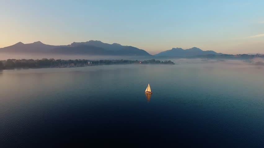 4K sunrise drone aerial shot of a sailingboat in the bavarian chiemsee lake, Panoramic View of the lake and the Alps in the golden hour, Mountains in the foggy sunrise