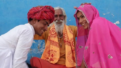 Hindu Sadhu blessing a newly wed couple in traditional dress, everyone looking at camera