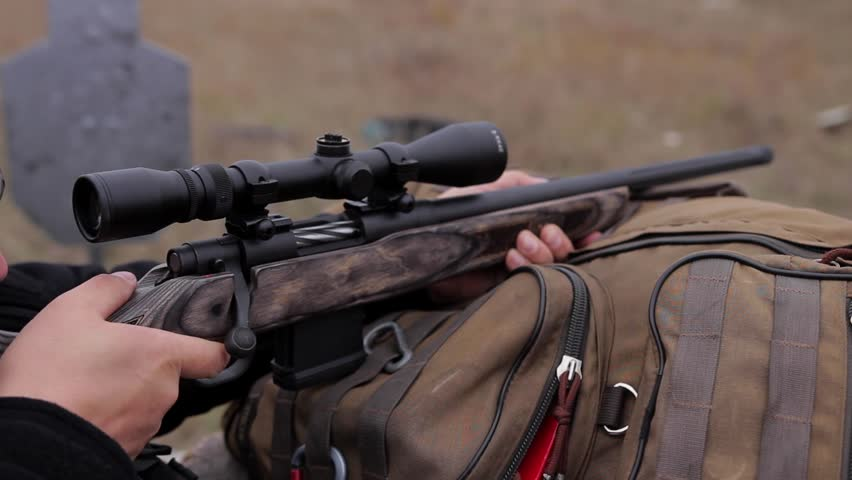Man in hunting equipment hold hunting rifle with a telescopic sight and shoot the target on firing range, close up.