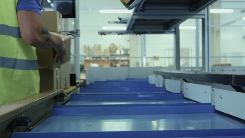 Parcels are Moving on Belt Conveyor at Post Sorting Office. Box POV.  Shot on RED Cinema Camera in 4K (UHD).