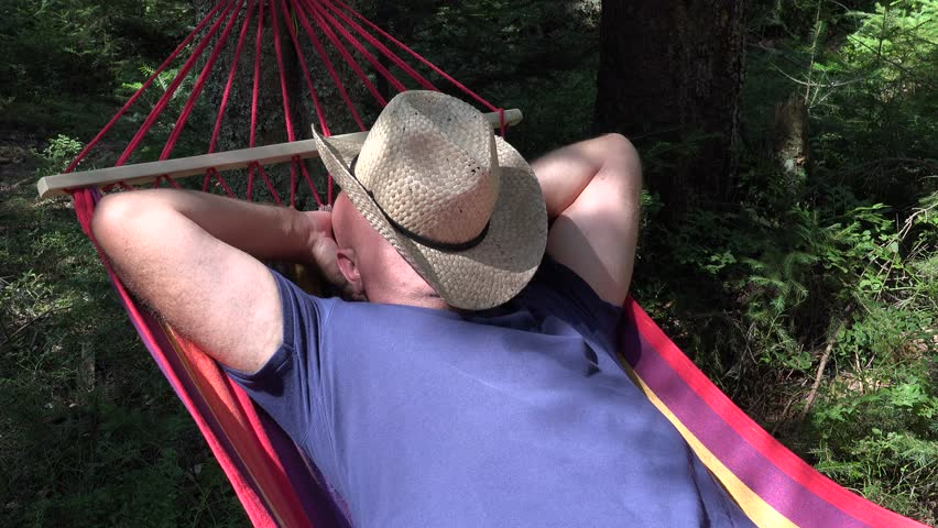 Tired Ranch Farmer Sleeping Deep and Dreaming with Hat covering Face in Tourist Hummock.