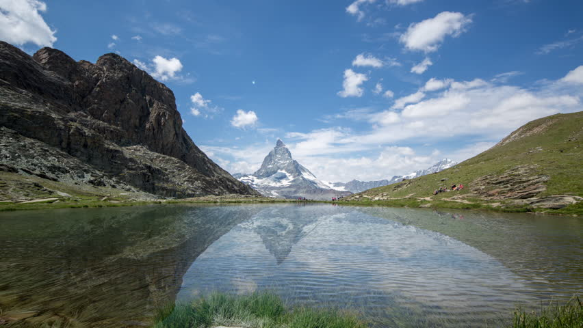 timelapse of the amazing matterhorn and surrounding mountains and lake in the Swiss Alps with fantastic cloud formations