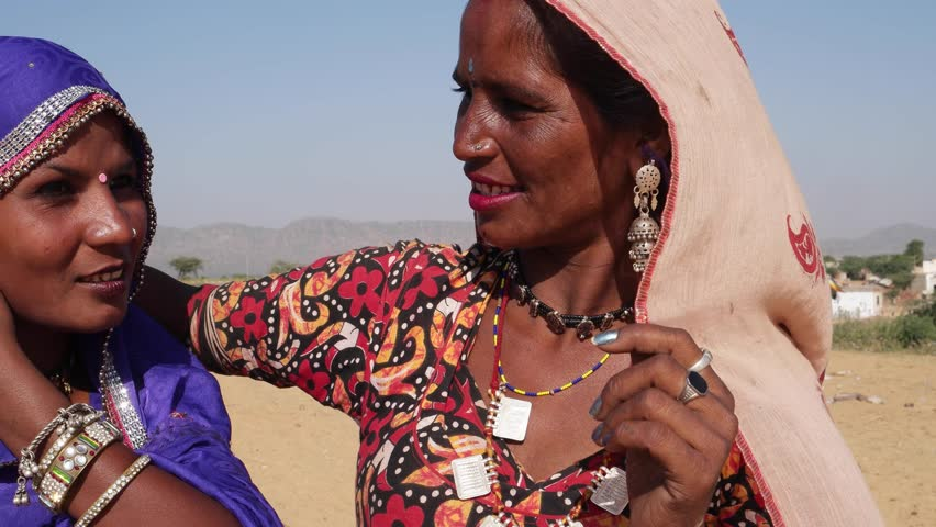 Close up of Two Indian women friends chatting with each other in bright outdoor sun in summer