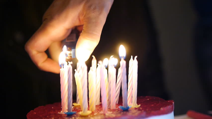 Hand Lighting A Birthday Candle On Cake
