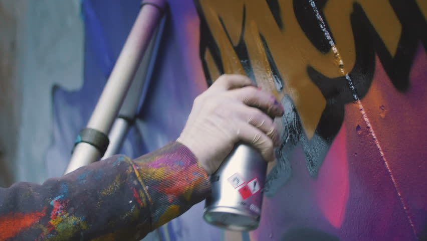 Graffiti  artist painting on the wall, exterior, close up