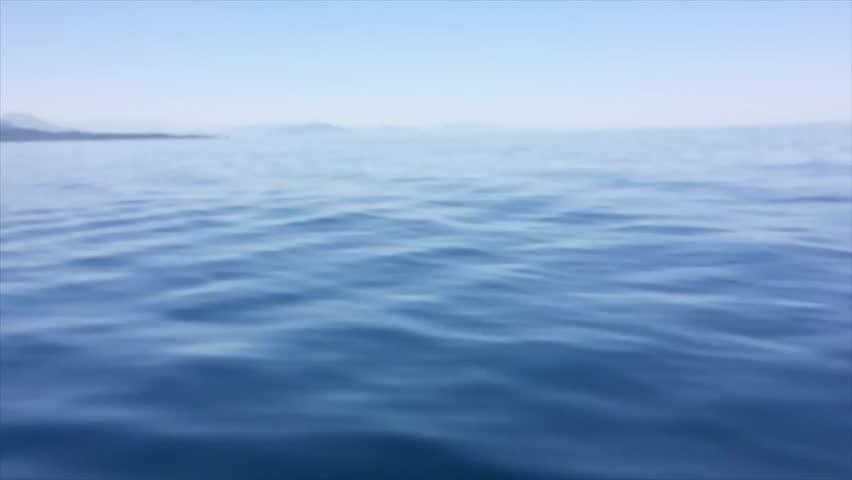 Calm sea and blue clear sky. Land so far