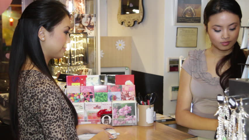 MEDIUM SHOT Customer paying in shop and receiving shopping bags