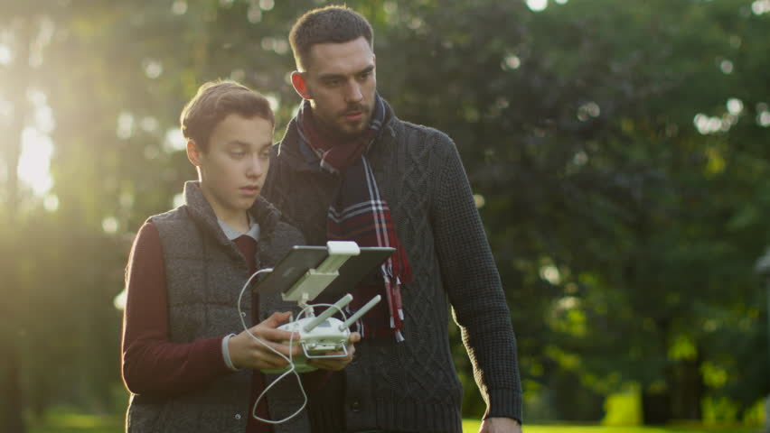 Father and Son Controlling Dron with Remote Control in the Park. Shot on RED Cinema Camera in 4K (UHD).