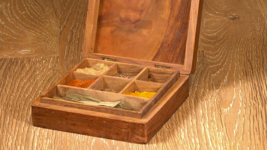 Collection of different oriental indian curry spices in wooden box with  cinnamon bark being picked up in senior man hand 1c7218c4ce16