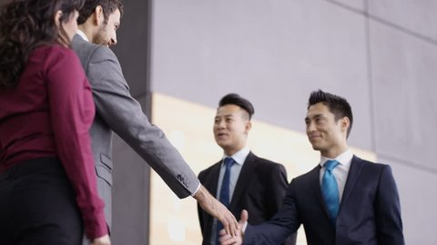 4K Business teams greet each other and shake hands in modern office building (UK-Oct 2016)