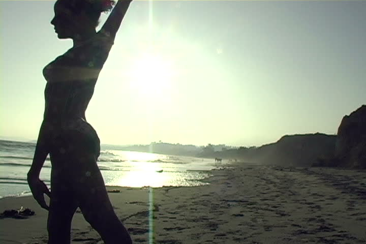 A beautiful, silhouetted young woman performs on the beach.