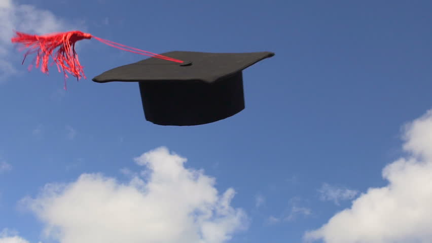 Students throwing mortarboards with tassels in blue sky, celebrating graduation
