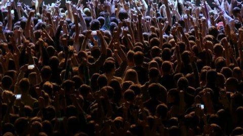 rock music fans clap wave hands dance under flashing colourful lights at concert upper backside view