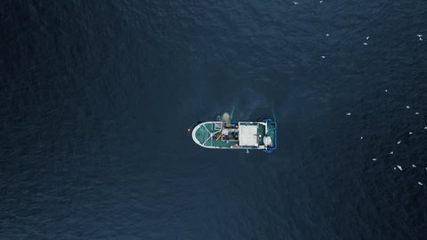 Zoom out of a Commercial Ship Fishing with Trawl Net on the Sea. Top down view. Shot on Phantom 4K UHD Camera.