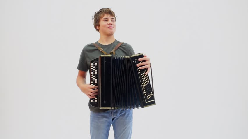 Young boy plays on accordion and smiles at white background