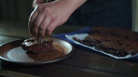 Chocolate brownie on plate. Chef serve chocolate dessert on plate. Man hands put chocolate cake pieces on ceramic plate. Serving cake. Homemade brownie cake on plate