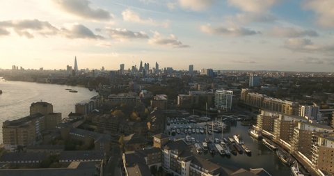 Aerial push out view of Limehouse basin with the skyline of the City of London in the background