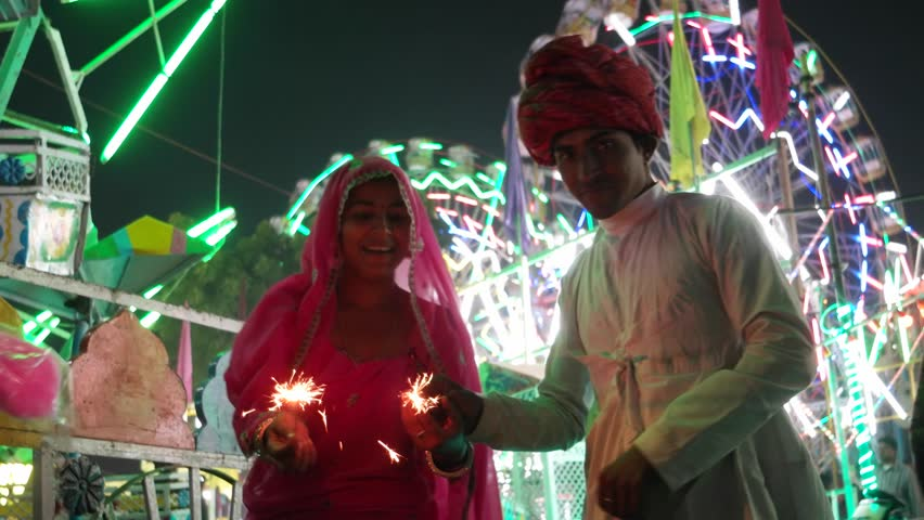Indian couple in traditional dress with fire sparkle cracker at Diwali Mela festival in India