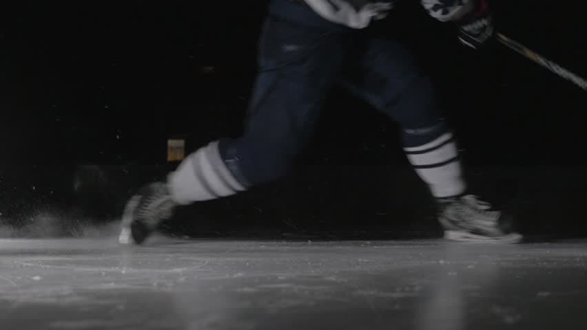 Ice hockey player shoots the puck in dark, power slap shot in canadian style by professional athlete.
