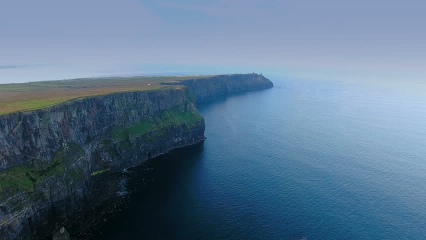 The amazing scenic view of the CLiffs of Moher fronting the big sea in West Ireland and the blue sky