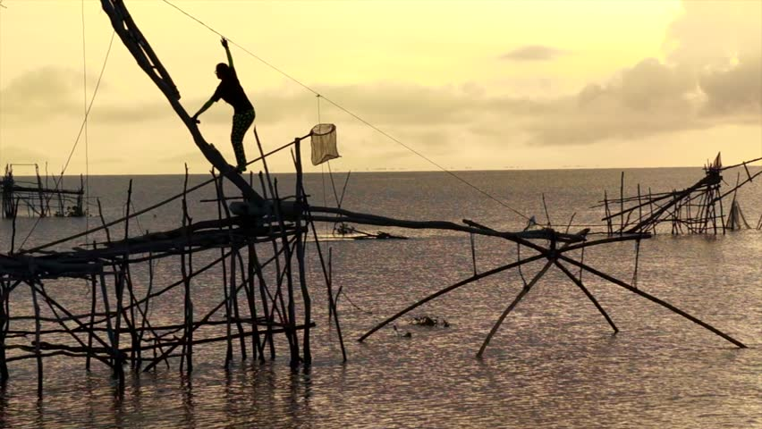 Silhouette of a fisher-woman using Net Trap called 'Yor' at Pak Pra Village Phatthalung, Thailand.Image contain certain grain or noise and soft focus