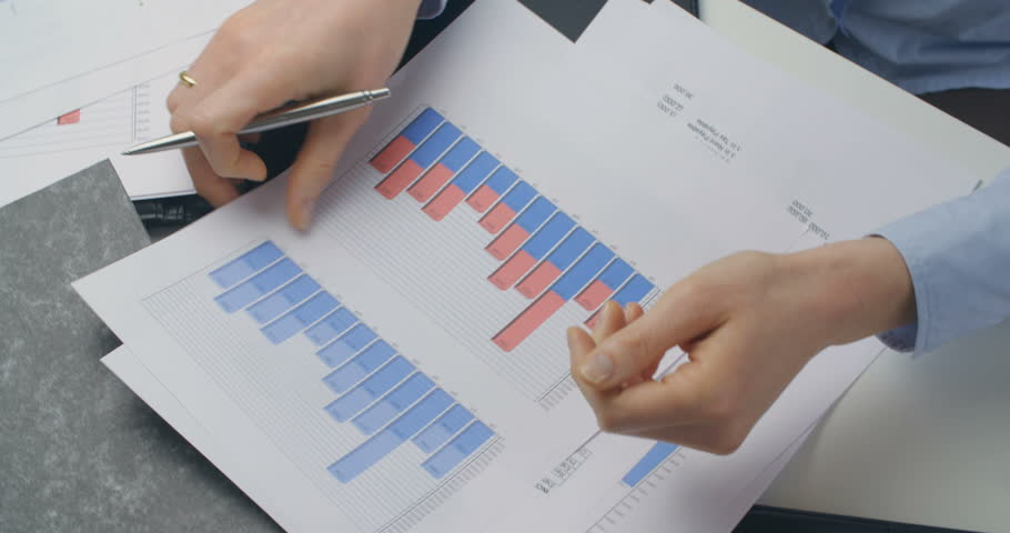 Top view of a female accountant reading documents with charts and financial information.   Shutterstock HD Video #21989839
