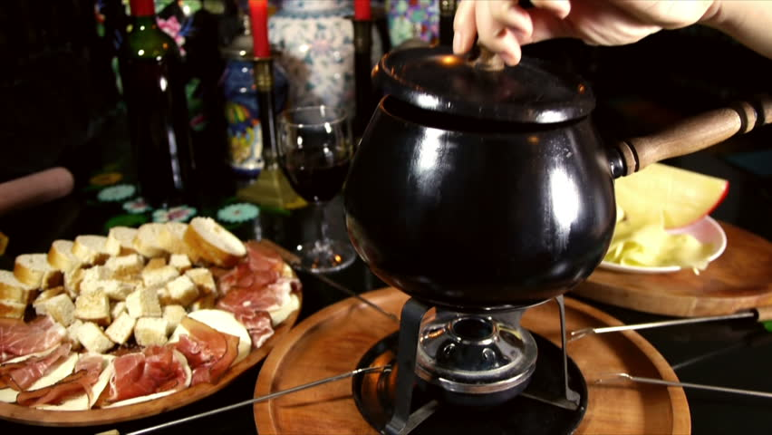 Swiss Fondue Sequence (HD). Fondue dinner table with bread, cheeses and ham with forks and candles shot on a sequence with different angles.