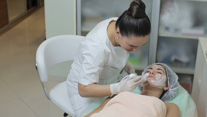 High angle view of woman lying on the couch in cosmetic cabinet while beautician in medical gloves doing skin treatment with ultrasonic machine | Shutterstock HD Video #22015645