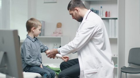 Male Doctor Removes Plaster from a Boy's Healed Hand. Boy is Very Happy . They Do High Five. In Slow Motion.