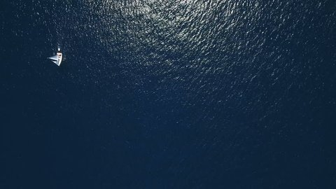 Aerial - Top down view of a deep blue sea rippling water surface reflecting the sunlight with a sail boat sailing by