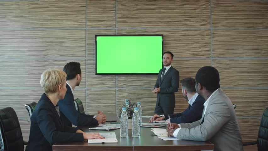 Lockdown of Asian businessman standing before LED TV screen with green chroma key background and showing presentation to colleagues sitting at table in conference room