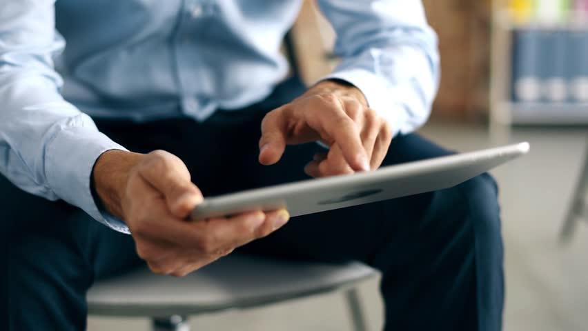 Businessman browsing his digital tablet   Shutterstock HD Video #22050658